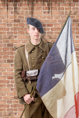 old flag: a 1940 french soldier with a flag , wall of red brick at the back Stock Photo