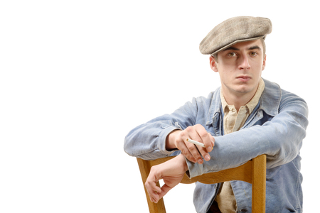 postwar: a young worker in vintage clothing, sitting on a chair on a white background Stock Photo