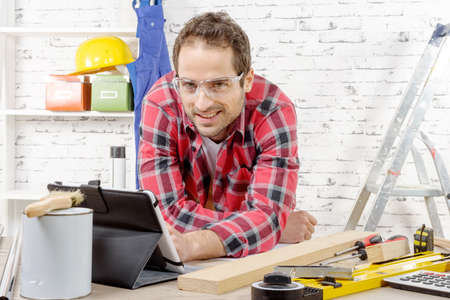 smilling: a smilling young man using the tablet for DIY