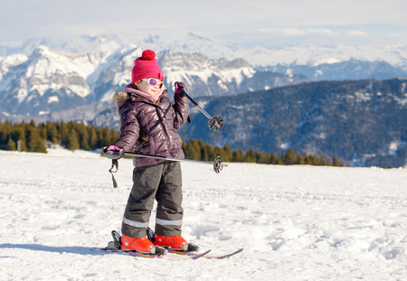 downhill: a happy little girl skiing downhill