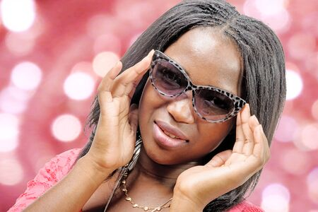 sexy black woman: a portrait of beautiful African American  young woman with sunglasses, bokeh in background