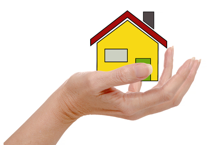 white house: the  small house in human hand, isolated on the white background Stock Photo
