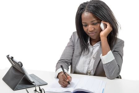 african american woman: an african american business woman writing and phone Stock Photo