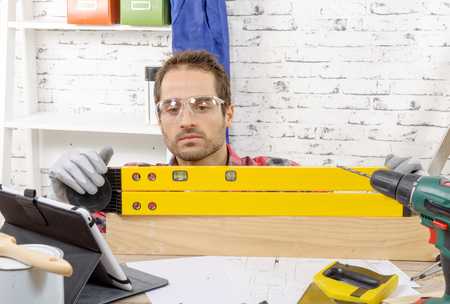 ensure: a young man viewing a spirit level,  to read the position of the bubble to ensure a horizontal line Stock Photo