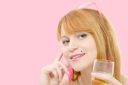 wine  pink: a pretty redhead woman drinks a glass of wine, pink background