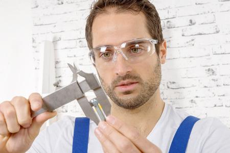 calipers: a young man measuring screw using caliper Stock Photo