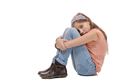 pre adolescent girl: a preteen girl sad  is sitting on the floor