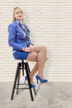 a pretty young blond woman with a blue suit, sitting on a stool