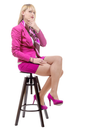 a pretty young blond woman with a pink suit, sitting on a stool Stock Photo