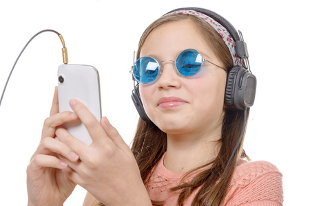 pre adolescent girl: A preteen girl listening to music with his smartphone, on white