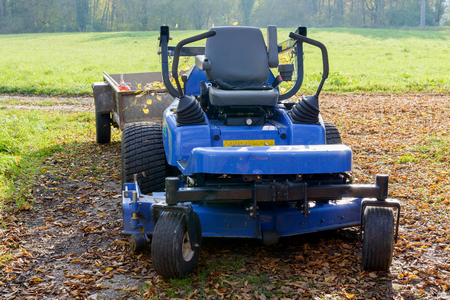 garden lawn: blue lawn mower in the middle of a meadow Stock Photo