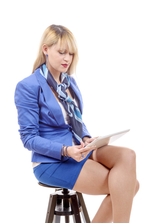 a pretty young blond woman with tablet, sitting on a stool