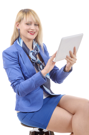 suit skirt: a pretty young blonde woman with a tablet, sitting on a stool
