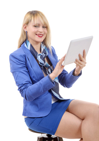 a pretty young blonde woman with a tablet, sitting on a stool