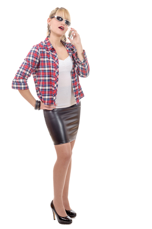 beautiful woman clothed in a leather skirt and shirt, on phone