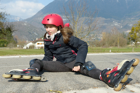 crick: young attractive teenage skater grimacing in pain after taking a fall on the asphalt