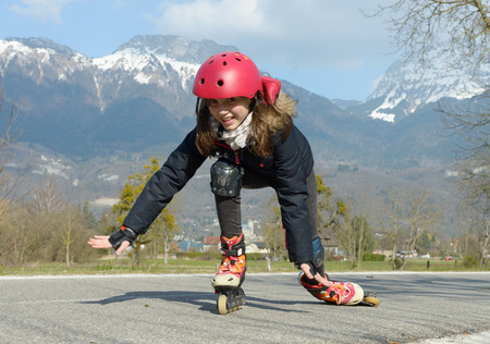 inline skater: a pretty preteen girl on roller skates in helmet at a track Stock Photo