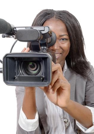een jonge Afro-Amerikaanse vrouwen met professionele videocamera op een witte achtergrond Stockfoto