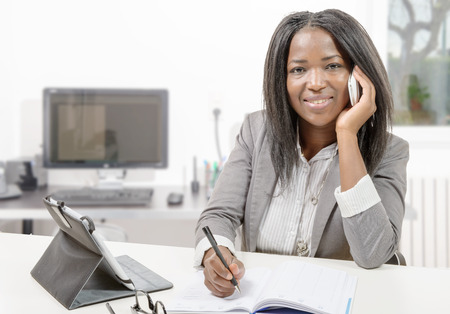 african business: a african american business woman working with tablet and phone