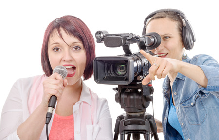 a young woman journalist with a microphone and camerawoman Imagens