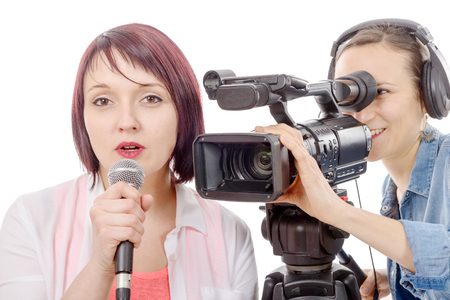 correspondent: a young woman journalist with a microphone and camerawoman Stock Photo