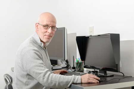 old desk: a mature man working with his computer Stock Photo
