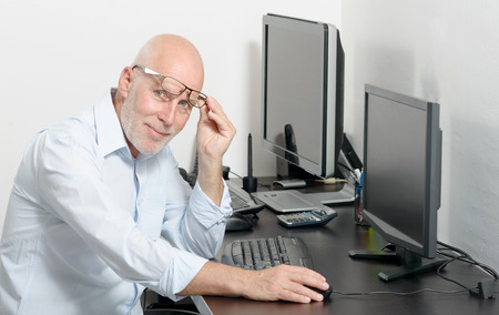 his: a mature man working with his computer Stock Photo