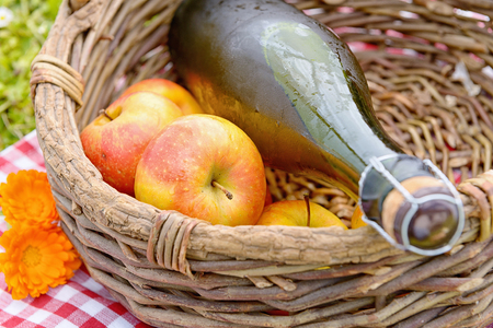 a bottle of cider with apples in a basket Stock Photo