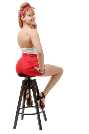 sit: beautiful girl in red shorts sitting on a stool isolated on white background