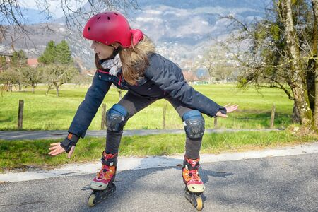 inline skater: pretty preteen girl on roller skates in helmet at a track Stock Photo