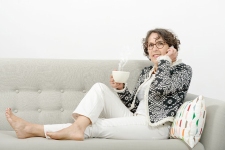 mature woman with phone, drinking tea on the sofa Imagens