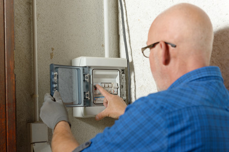 meter box: a mature man working with electric box at house