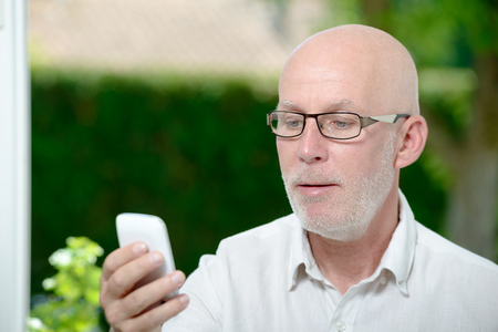 phone message: a senior man reading message on smartphone