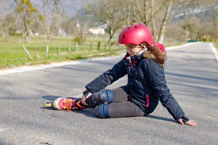 young attractive teenage skater grimacing in pain after taking a fall Foto de archivo