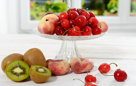 kiwis: cherries, and peaches in a glass cup with  some kiwis