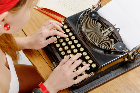 closeup of hands of a young woman with an old typewriter