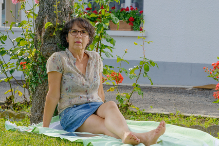 middleaged: middle-aged woman with glasses is resting in the garden