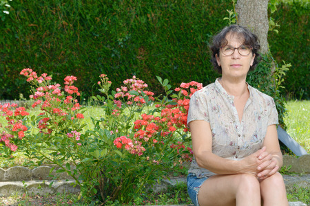 mature woman sitting: a portrait of a mature woman sitting in garden