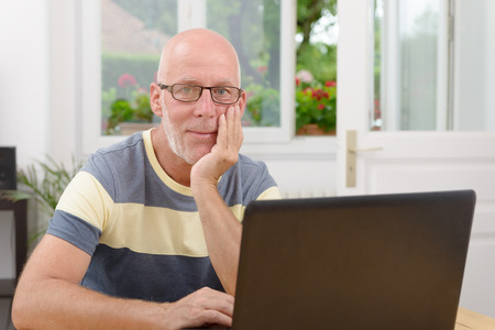 a middle-aged man with a laptop Stock Photo