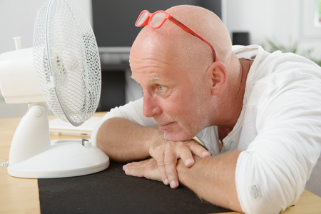 refreshed: a mature man refreshed with a fan