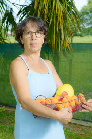 a mature woman with a blue dress and a fruit basket Stock Photo