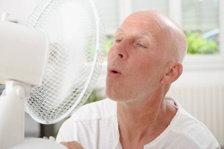 refreshed: mature man refreshed with a fan in his home Stock Photo