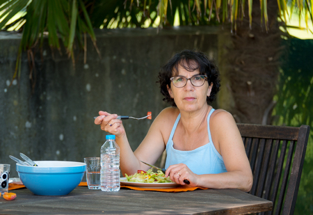 a mature woman lunch in the garden