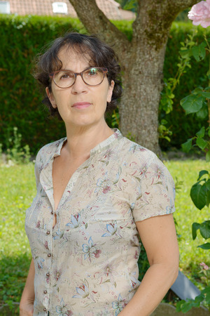 a portrait of a mature woman with glasses in his garden
