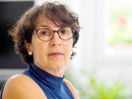 portrait of a beautiful mature woman with glasses Фото со стока
