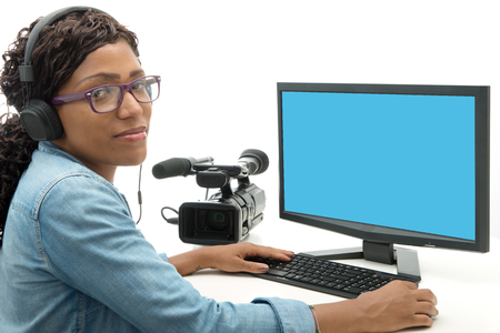 editor: young African American woman video editor with computer and camcorder Stock Photo