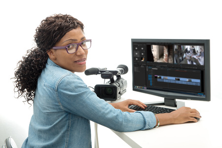 young African American woman video editor with computer and camcorder Foto de archivo