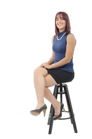 pretty young woman sitting on a stool isolated on white background Stock Photo