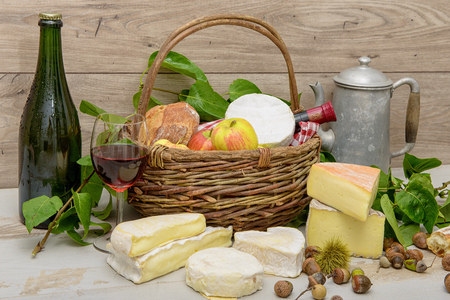 several: several french cheeses with a bottle of cider