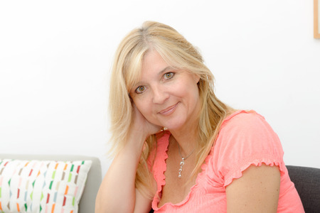 cocooning: a portrait of mature smiling blond woman